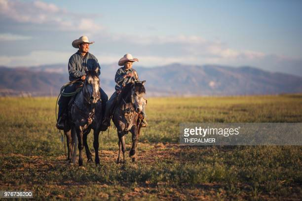 father and son horseback riding - rancher stock pictures, royalty-free photos & images