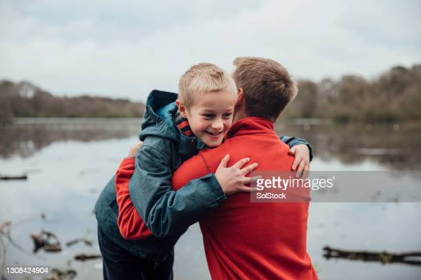 father and son hugging - genderblend stock pictures, royalty-free photos & images