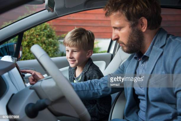 Father and son in a car searching on gps