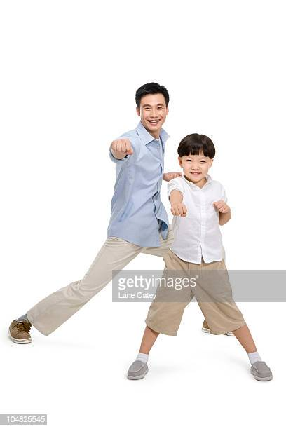 father and son in a kungfu pose - fighting stance stock pictures, royalty-free photos & images