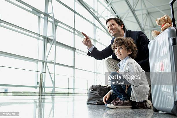 Father and son (5-6) in airport lobby