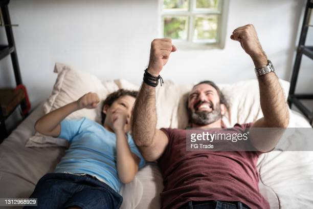father and son in bed playing pretending to be driving - genderblend stock pictures, royalty-free photos & images