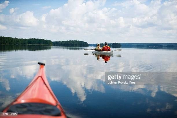 Father and son in canoe paddling across lake Immeln Skane Sweden.