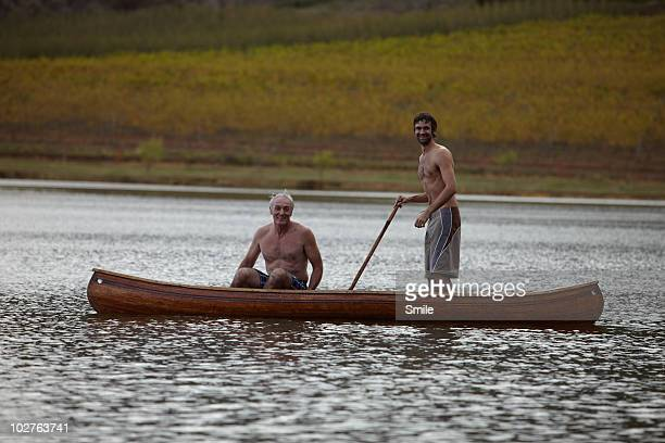 Father and son in costumes in canoe, son standing