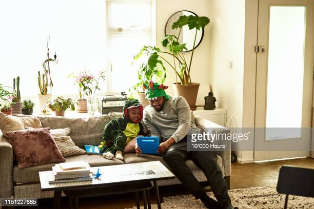 Father and son in dragon costumes using tablet on sofa