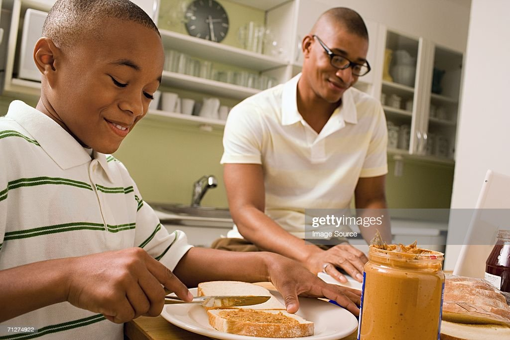 Father and son in eating in kitchen : Stock Photo