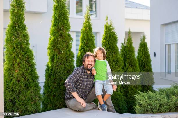 Father and son in front of their big modern house