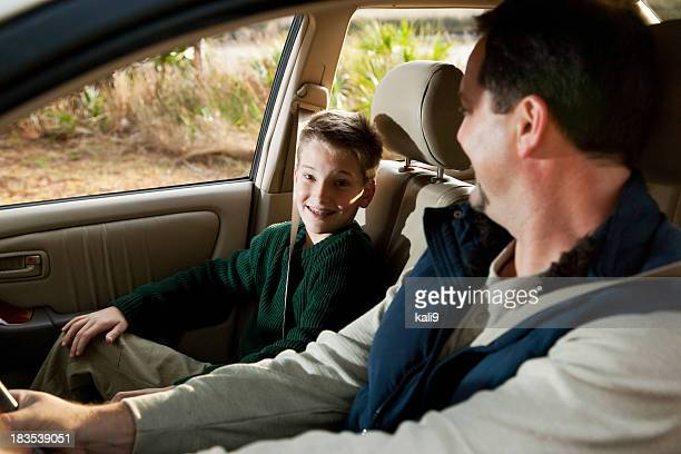 Father and son in front seat of car
