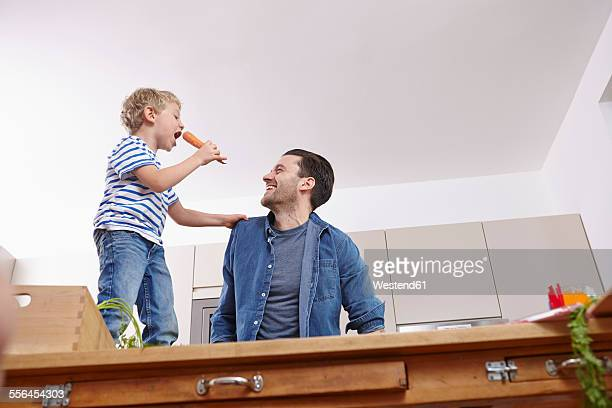 Father and son in kitchen, boy singing on table holding carrogt