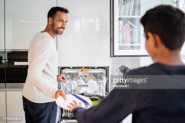 father and son in kitchen clearing dishwasher together - mid volwassen mannen stockfoto's en -beelden