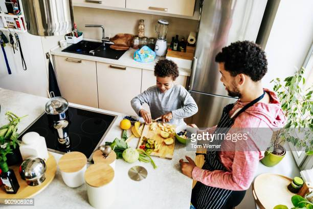 Father And Son In Kitchen Preparing Salad Together