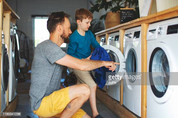father and son in laundry - launderette stock pictures, royalty-free photos & images