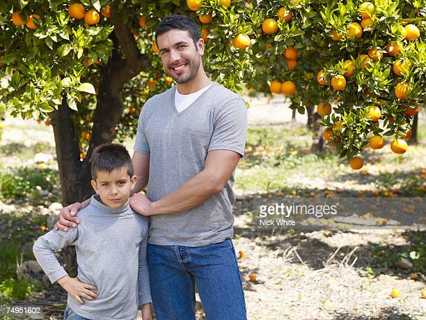 Father and son (6-8) in orchard, portrait