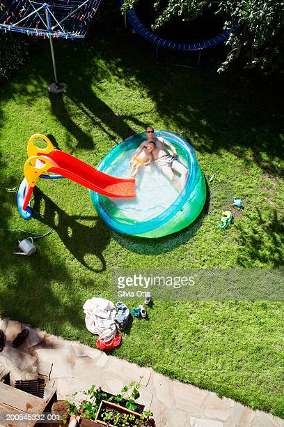Father and son (4-5) in paddling pool in garden, elevated view