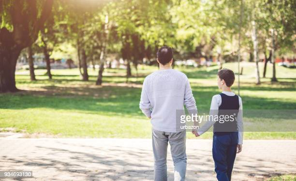 father and son in park - autism awareness stock pictures, royalty-free photos & images