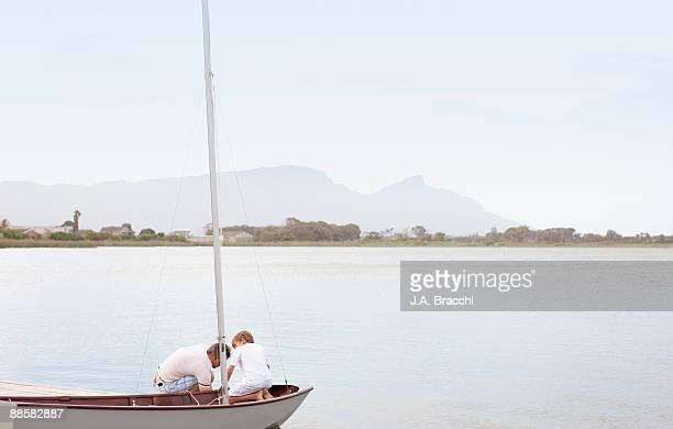 Father and son in sailboat on lake