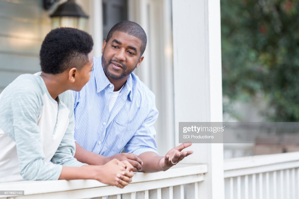 Father and son in serious front porch conversation : Stock Photo