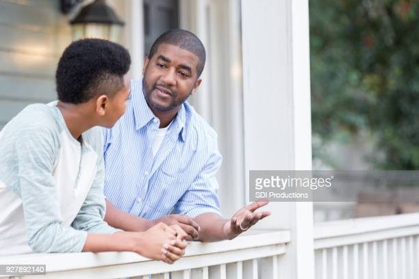 father and son in serious front porch conversation - genitori foto e immagini stock