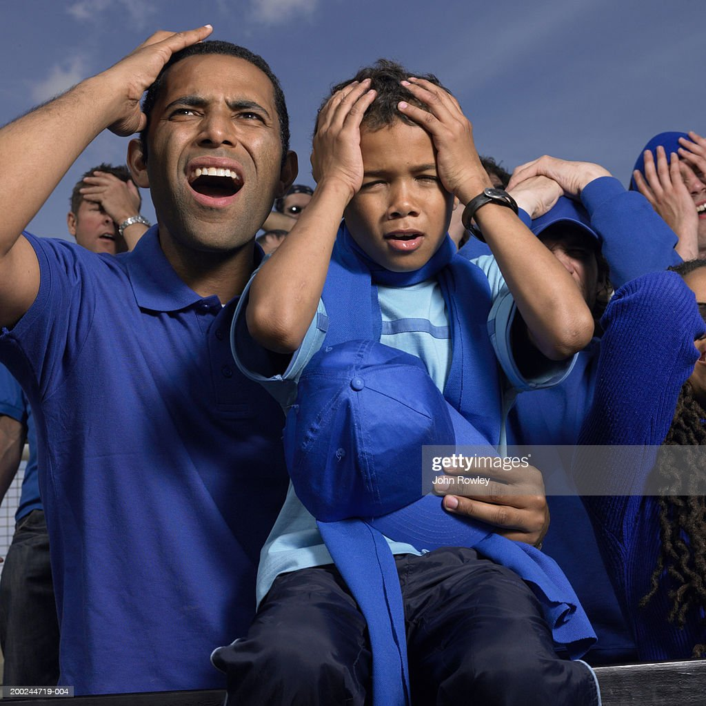Father and son (5-7) in stadium crowd, hands to heads, close-up : Stock Photo