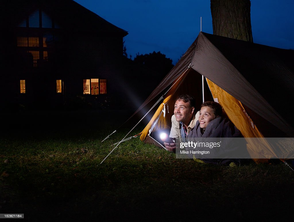 Father and son in tent shining torch in distance. : Stock Photo