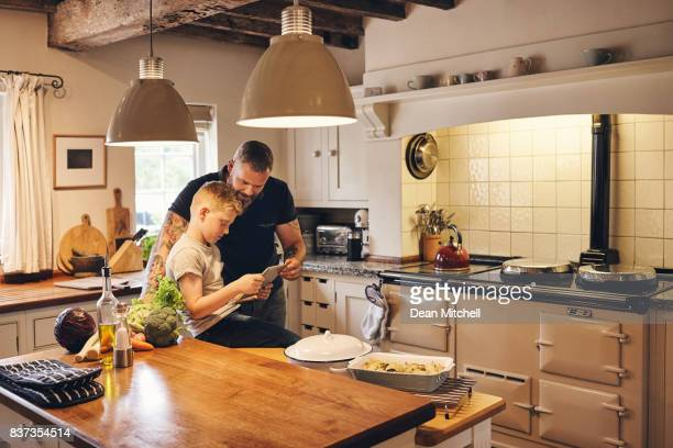 Father and son in the kitchen with digital tablet