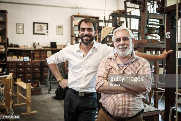 father and son in their artisanal handicraft traditional textile factory - two generation family stock pictures, royalty-free photos & images