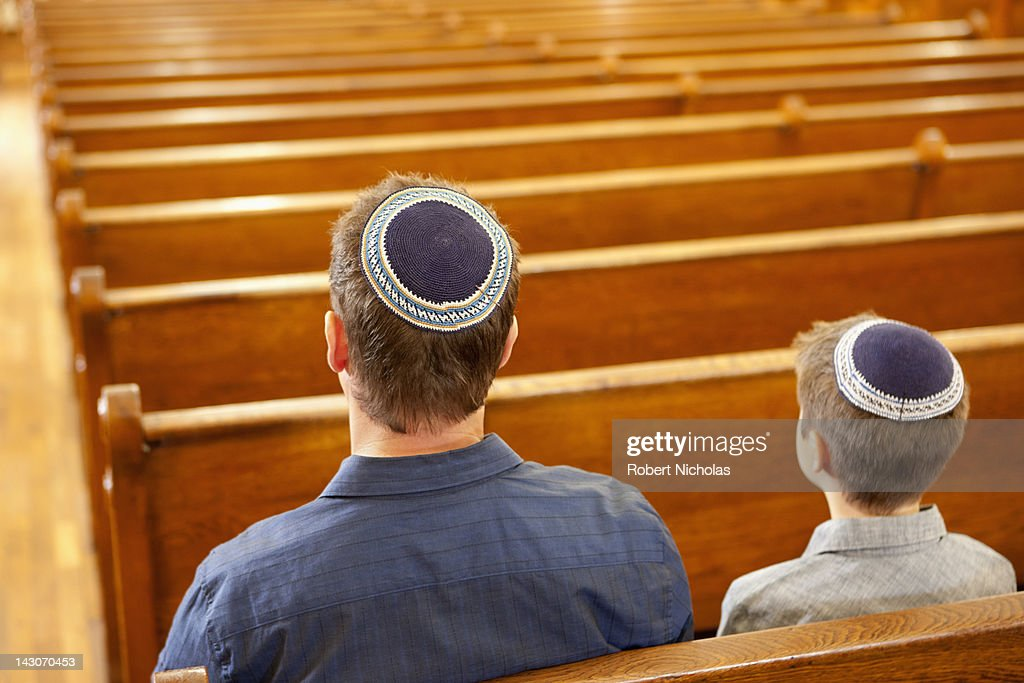 Father and son in yarmulkes sitting in synagogue : Stock Photo