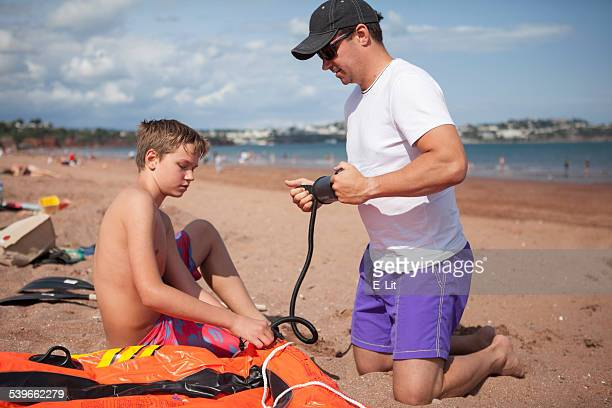 Father and son (12-13) inflating boat on beach