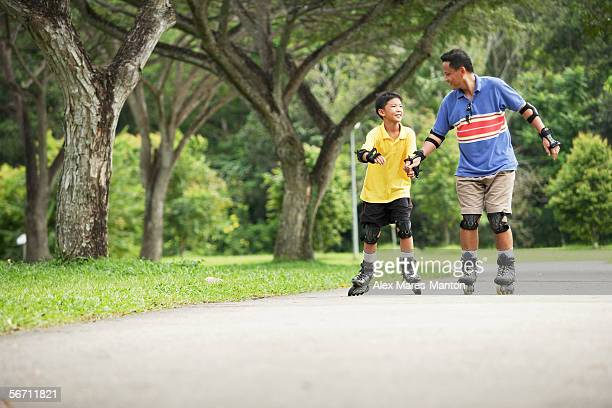 Father and son in-line skating in park, father holding son's hand