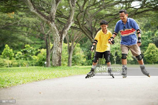 Father and son, in-line skating in park, holding hands