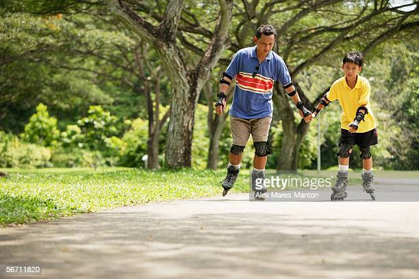Father and son in-line skating in park