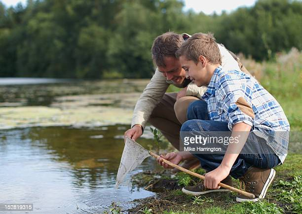 father and son inspecting fishing net. - eco tourism stock pictures, royalty-free photos & images
