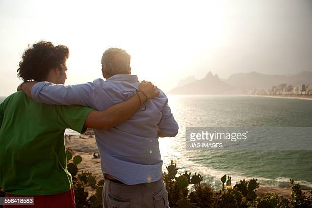 father and son, ipanema beach, rio de janeiro, brazil - brazilian men stock photos and pictures