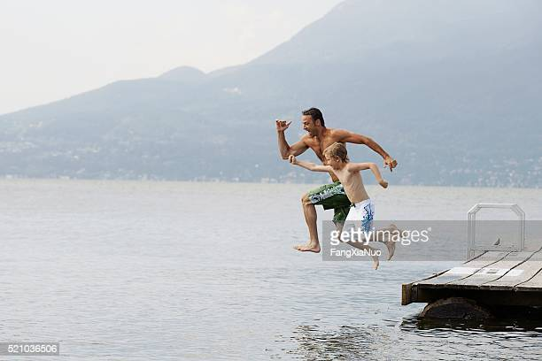 father and son jumping from dock - standing water stock pictures, royalty-free photos & images