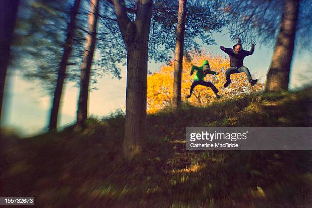 A father and son jumping in a forest