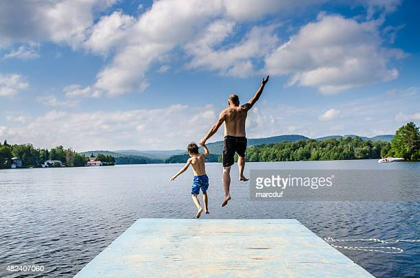 father and son jumping in lake - lake stock pictures, royalty-free photos & images