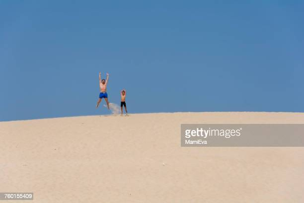 Father and son jumping in the air on the beach, Tarifa, Cadiz, Andalucia, Spain