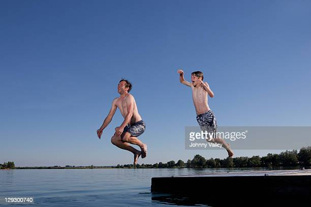 Father and son jumping into lake