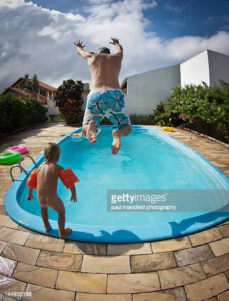 father and son jumping into pool - boxershort stock pictures, royalty-free photos & images