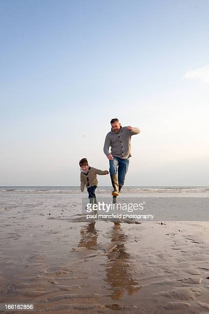 Father and son jumping on sandy baech