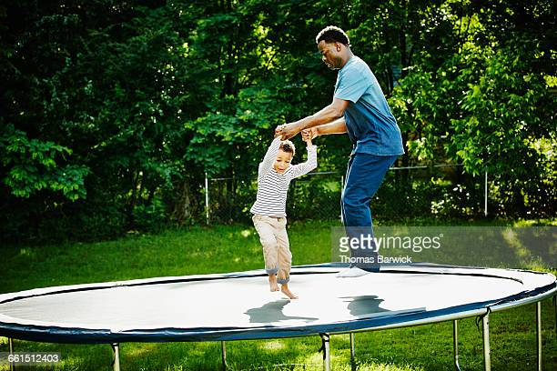 Father and son jumping together on trampoline