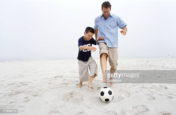 Father and son (12-13 years) kicking soccer ball on beach