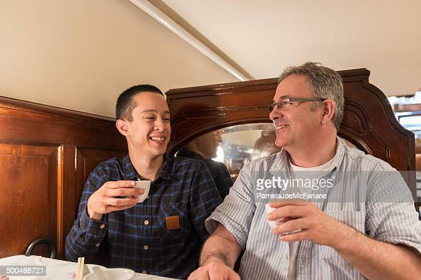 Father and Son Laughing and Drinking Tea