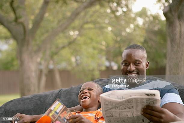 Father and son laughing and reading