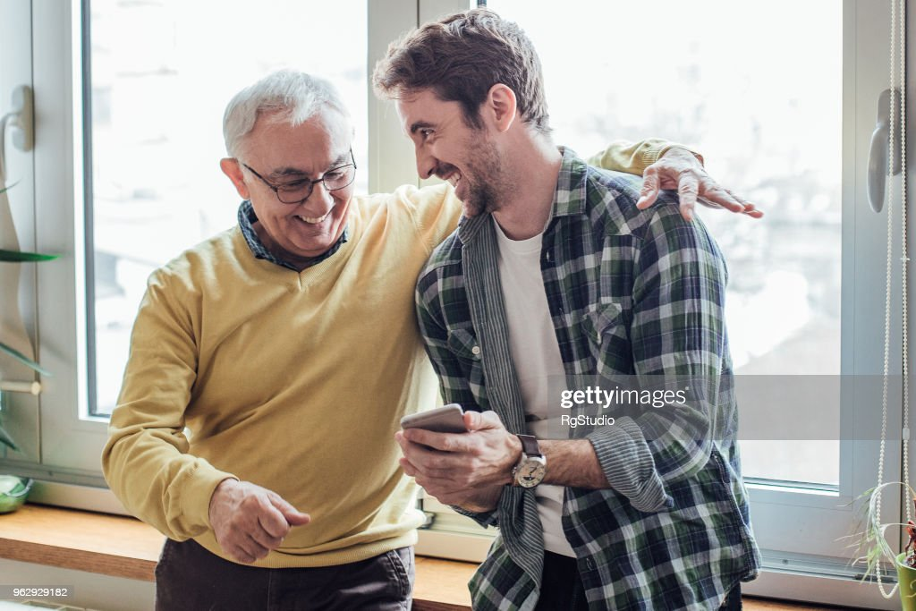 Father and son laughing and using phone : Stock Photo