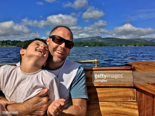 father and son laughing at camera whilst in boat on lake - one parent stock pictures, royalty-free photos & images