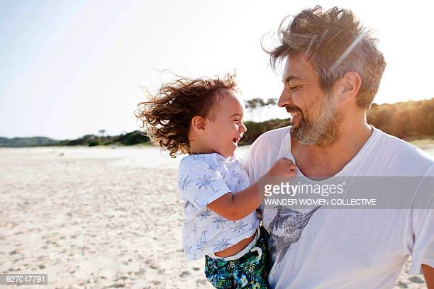 father and son laughing on the beach at sunset - candid beach stock photos and pictures