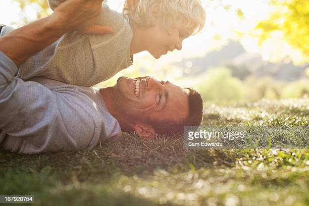 Father and son laying in grass together
