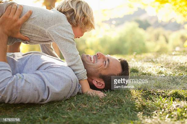 Vater und Sohn zusammen auf Gras Bauchlage
