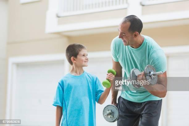 父と息子の手の重みを持ち上げる - kids weightlifting ストックフォトと画像